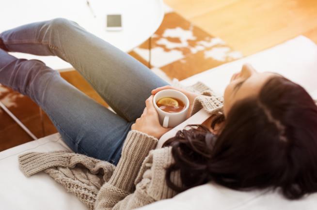 Una donna si rilassa sul divano con una tisana