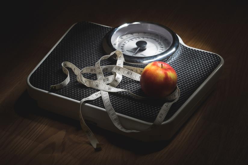 Una bilancia con sopra una mela.