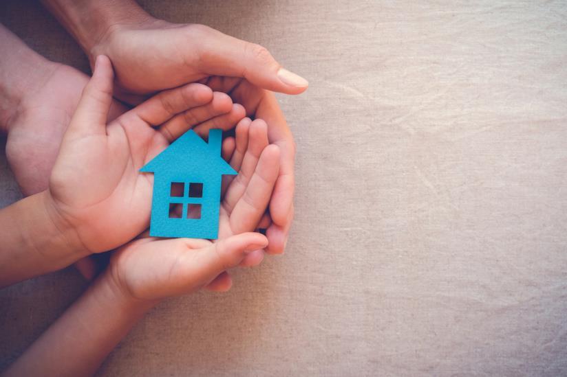 Mani che stringono la riproduzione in cartone di una casa
