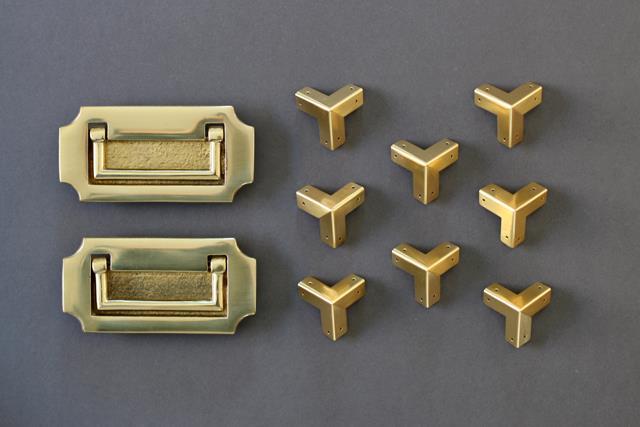 Maniglia di ottone e angoli di ottone disposti su una superficie blu