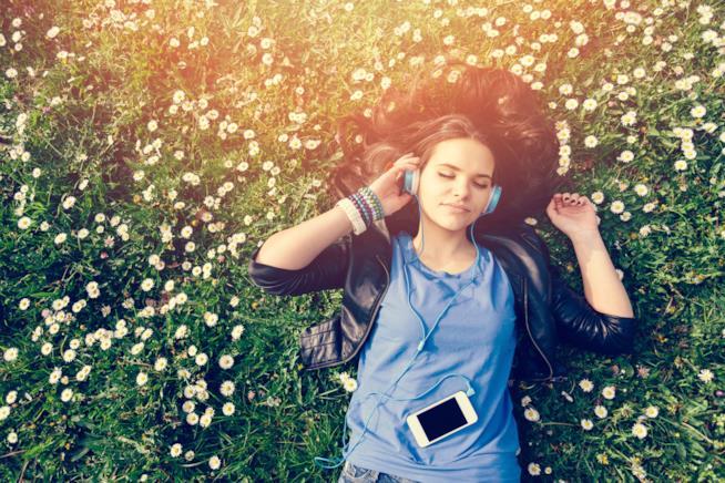 Una ragazza sdraiata in un prato si rilassa ascoltando musica