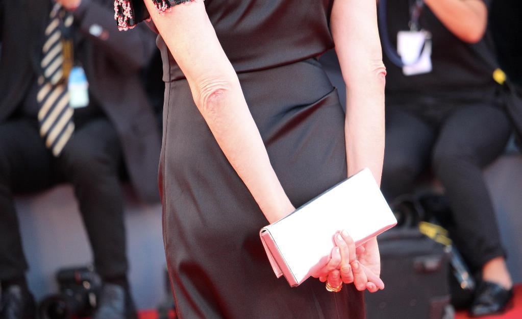 Annette Bening stringe una pochette metalizzata sul red carpet di Venezia 74.