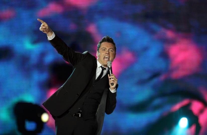 Tiziano Ferro, in piedi, vestito di nero, canta al microfono
