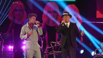 Fedez in grigio, J-Ax in nero cantano in piedi al microfono con lo sfondo del volto della Ferragni
