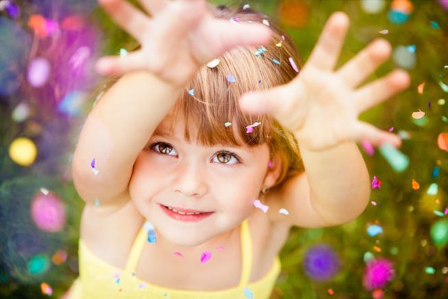 Primo piano di una bambina che cerca di afferrare dei coriandoli