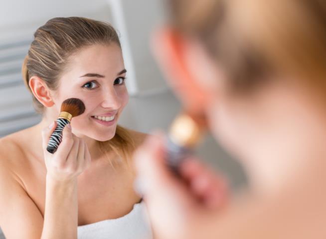 Ragazza allo specchio che applica il blush
