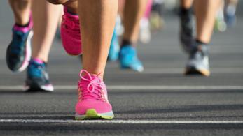 scarpe sportive rosa in primo piano e altre persone dietro sullo sfondo che corrono
