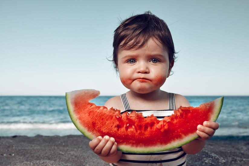Bambino con una fetta di cocomero in mano