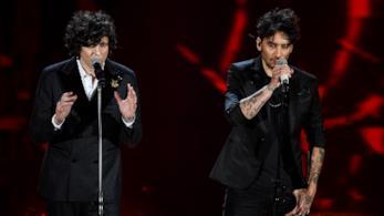 Ermal Meta e Fabrizio Moro, in piedi, cantano di fronte al microfono, vestiti di nero