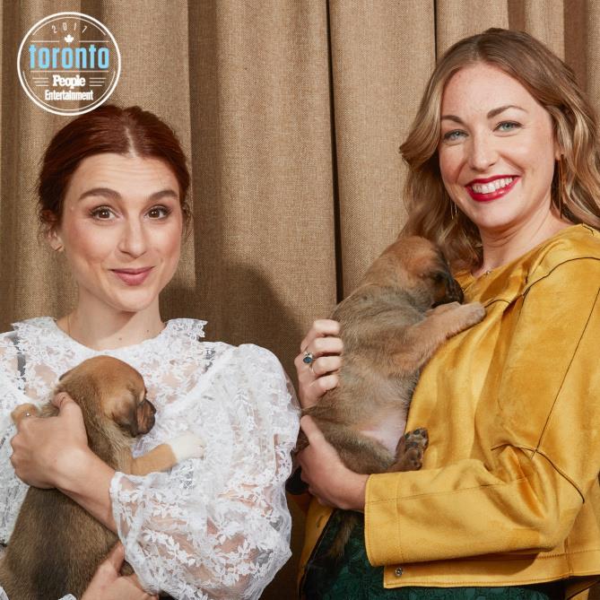 Aya Cash e Molly McGlynn  con dei cuccioli in braccio