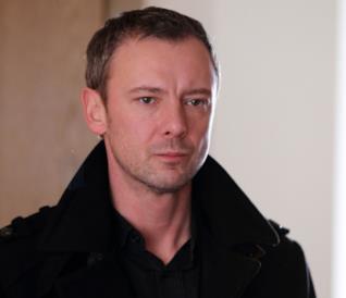 John Simm in primo piano con un giaccone nero