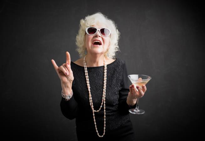 Una signora chic, con vestito nero elegante e collana di perle, fa le corna verso l'altro mentre tiene in mano un bicchiere di gin