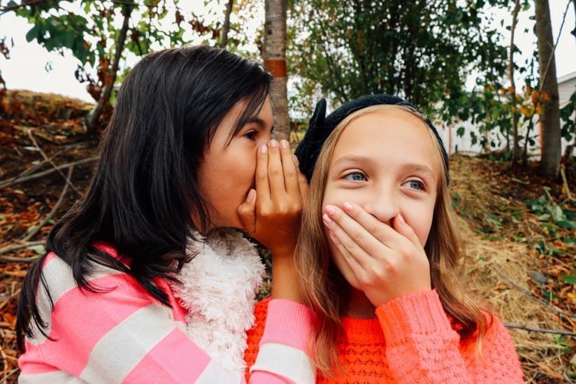 Una bambina che dice qualcosa nell'orecchio ad un'altra.