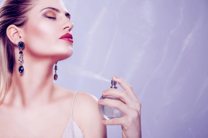 Donna che spruzza il profumo