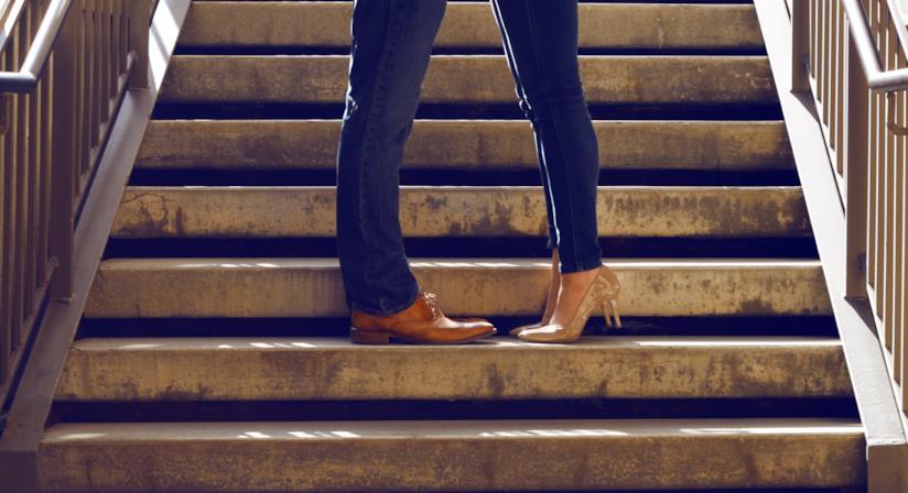 Dettaglio delle gambe di uomo e donna su una scala