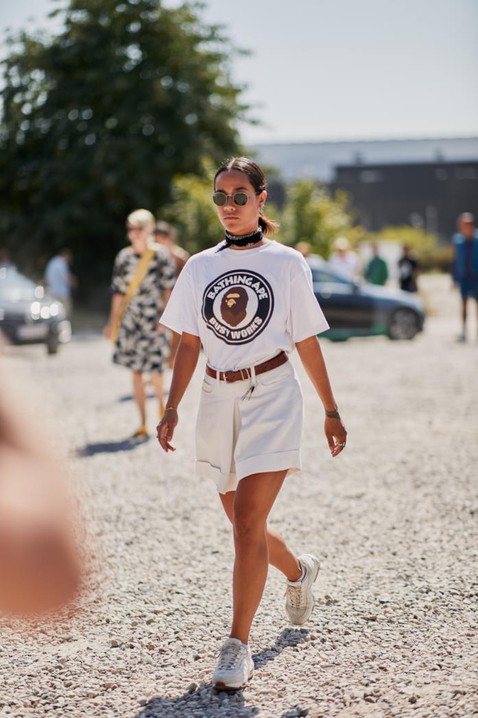 Sneakers indossate con bermuda bianchi e t-shirt