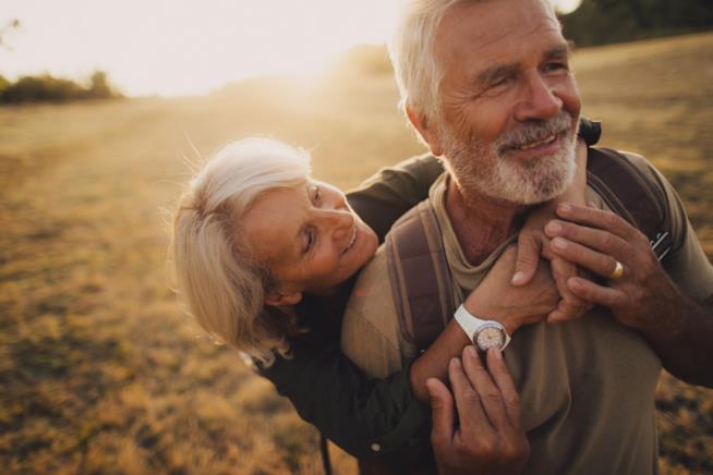Coppia di anziani si abbraccia sorridendo