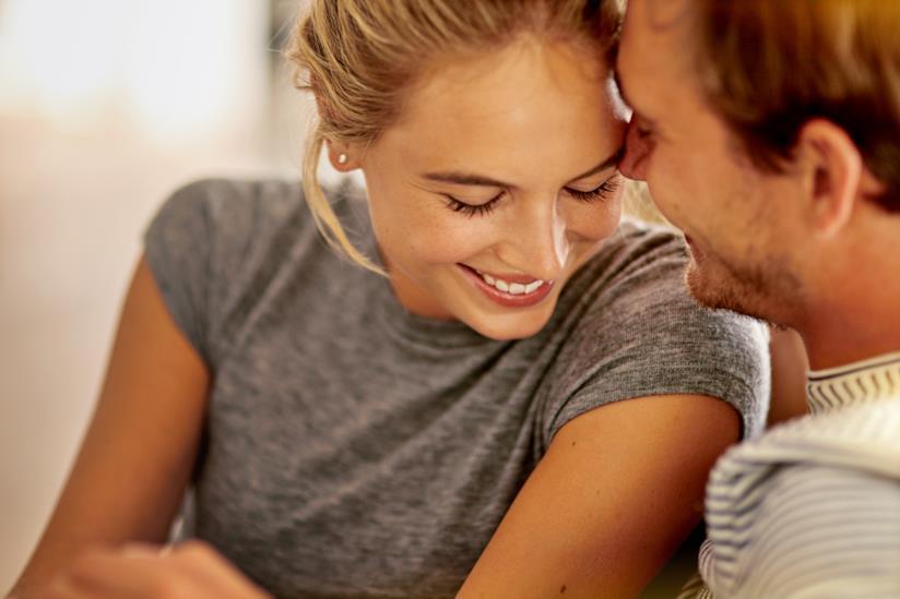 Una coppia sorride abbracciandosi