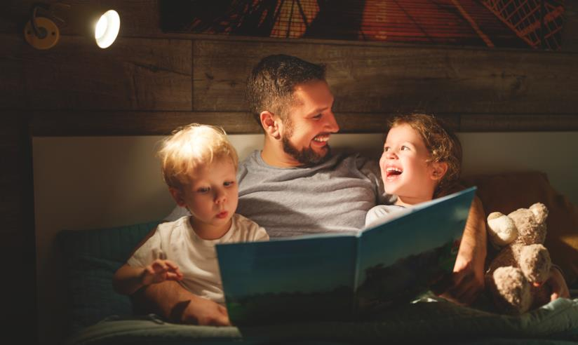 Padre con i due figli a letto di sera che legge una storia