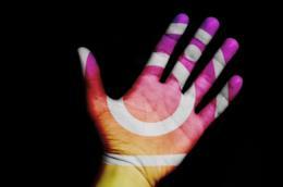 Una mano con i colori e il logo di Instagram.