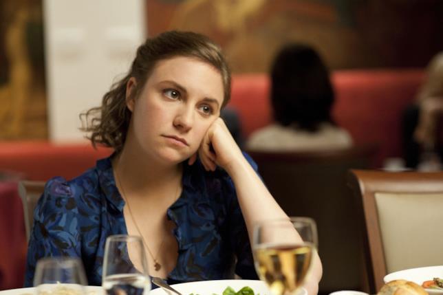 Hannah seduta a tavola con aria annoiata
