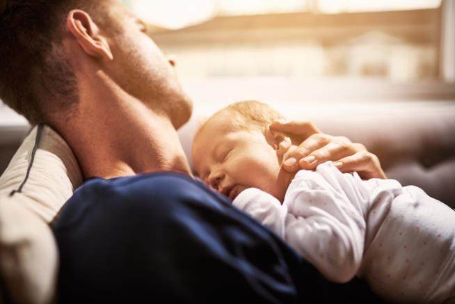 Un padre tiene un neonato in braccio, adagiato sul suo petto