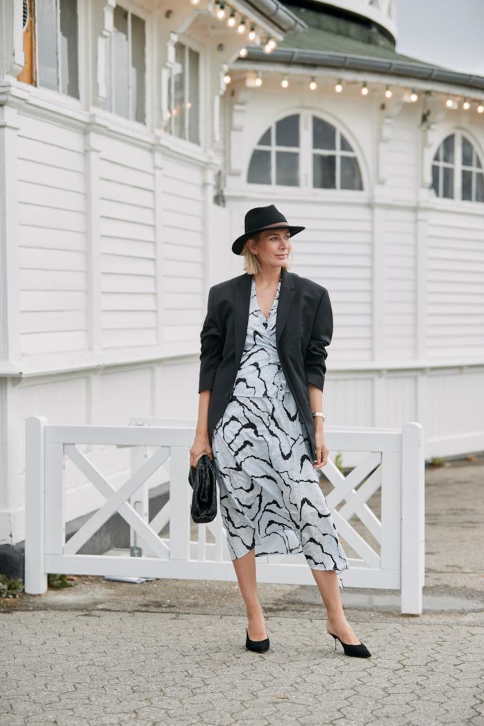 Blazer oversize abbinato a abito midi stampato e mules con tacco sottile