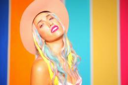 Nina Zilli con un cappello e i capelli colorati, davanti a uno sfondo colorato