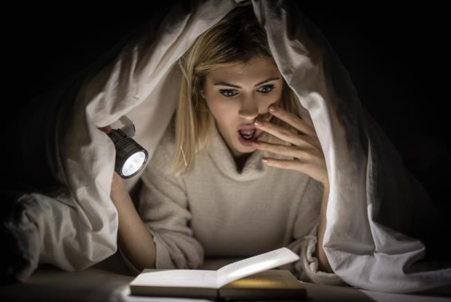 Ragazza legge un libro horror
