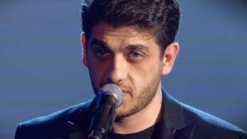 Mirkoeilcane, in nero, in piedi, di fronte al microfono