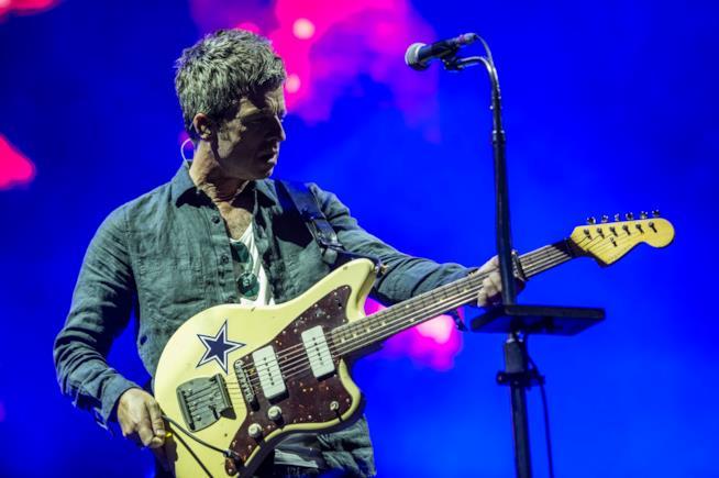 Noel Gallagher, in piedi, con una chitarra gialla in mano, su sfondo blu e di fronte al microfono