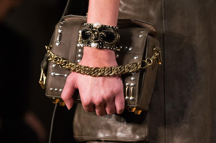 Una mano con un bracciale che tiene una borsetta