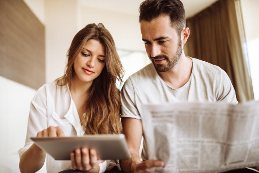 Una donna che usa il tablet, un uomo che legge il giornale.