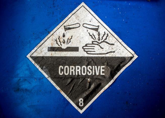 Segnale che avverte della presenza di sostanze corrosive