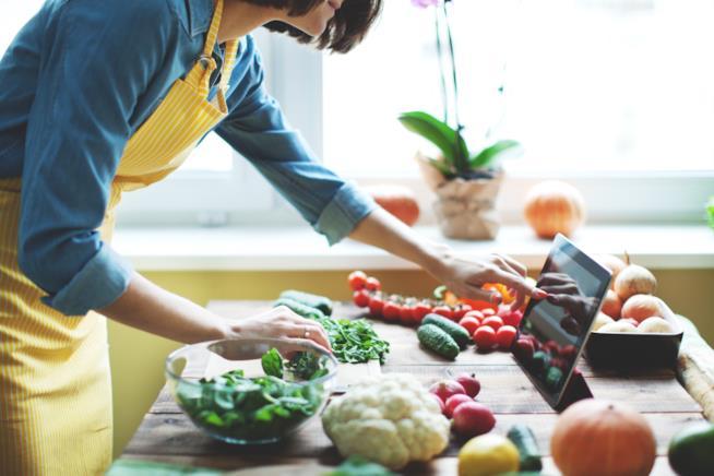 Una donna cucina seguendo la ricetta su un tablet