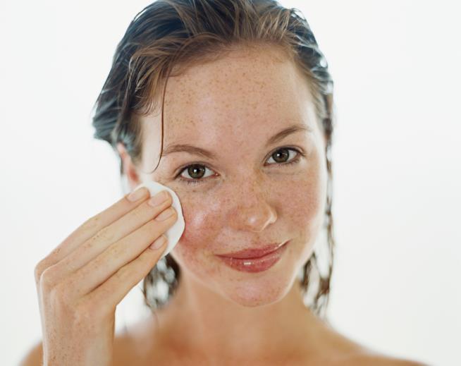 Primo piano di una bella ragazza mentre si deterge il viso con un dischetto di cotone