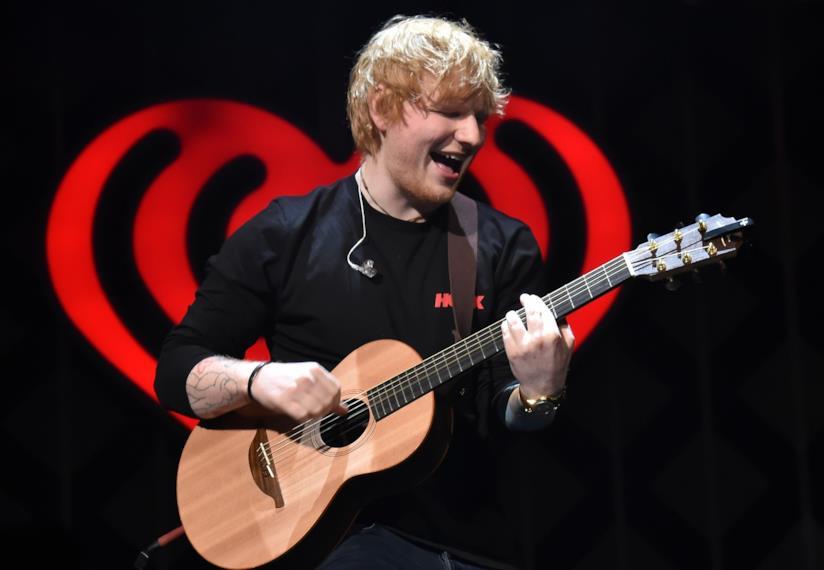 Ed Sheeran suona la chitarra acustica, sorridente, davanti a un cuore rosso su sfondo nero