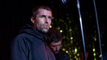 Liam Gallagher sopra il palco, davanti al microfono con in mano un tamburello