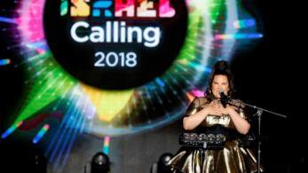Netta, di fronte al microfono, con alle spalle la scritta Israel Calling 2018
