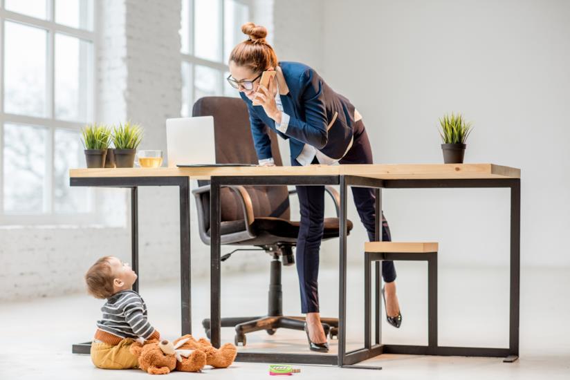 Una mamma che lavora mentre il figlio piccolo la guarda.