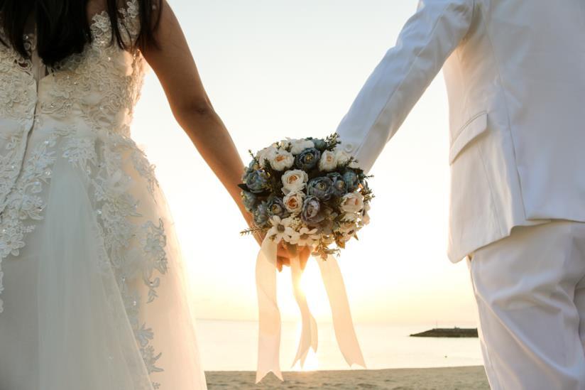 Due sposi che tengono i fiori in mano.