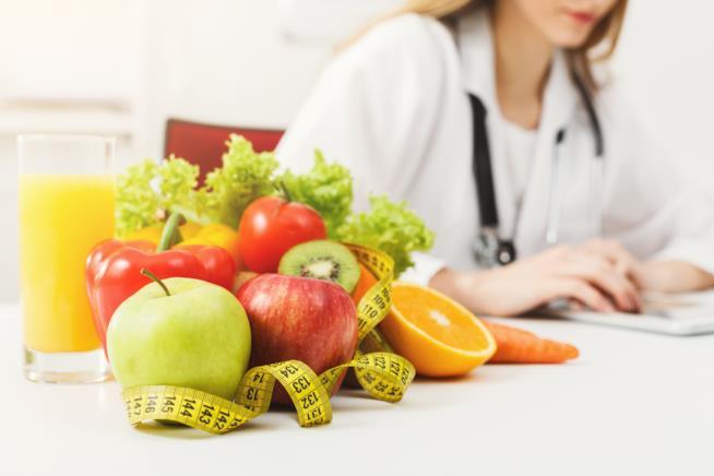 Della frutta in primo piano e una dottoressa in secondo piano.