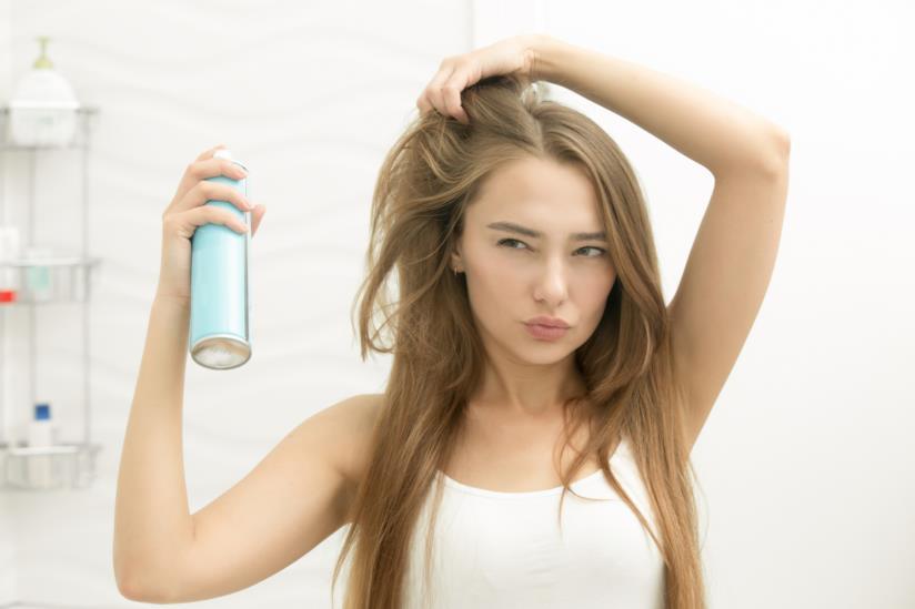 Ragazza con spray per capelli