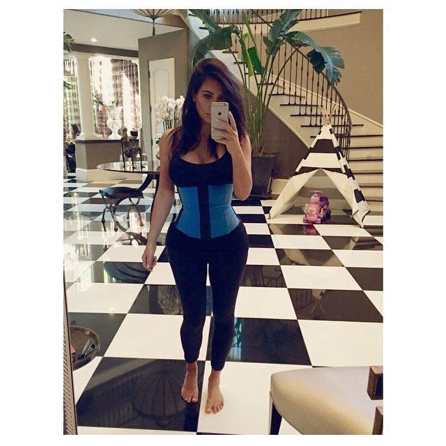 Kim Kardashian mentre scatta una foto di sé con il corsetto