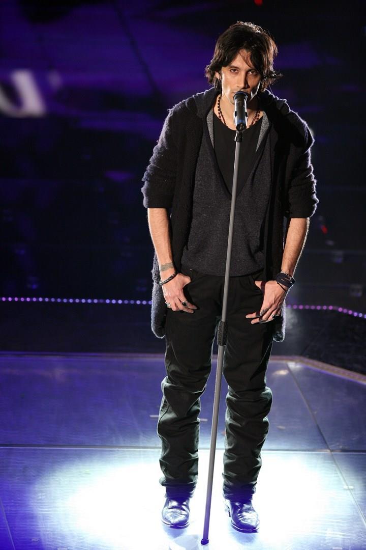 Fabrizio Moro, in piedi, di fronte al microfono, vestito di nero
