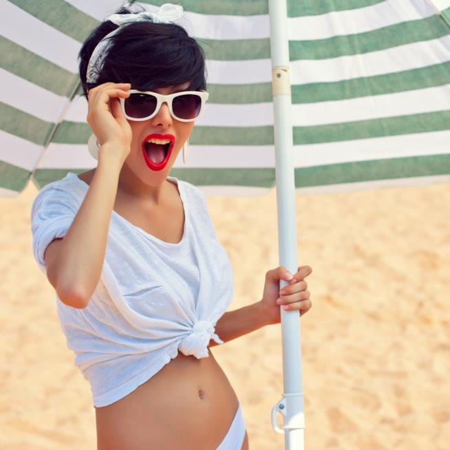 Una bella ragazza con i capelli scuri e corti, con occhiali da sole bianchi, sorride sotto un ombrellone in spiaggia