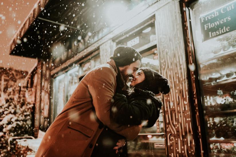 Due ragazzi abbracciati sotto la neve