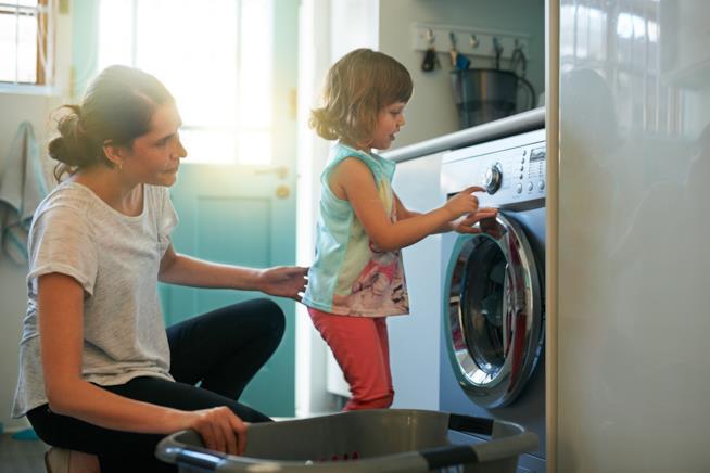 Bambina carica la lavatrice