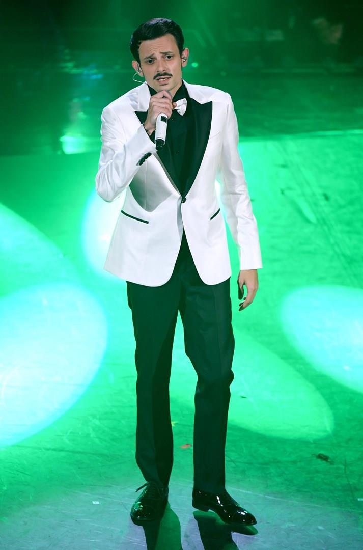 Fabio Rovazzi, con pantaloni neri e giacca bianca, canta in piedi al microfono su sfondo verde