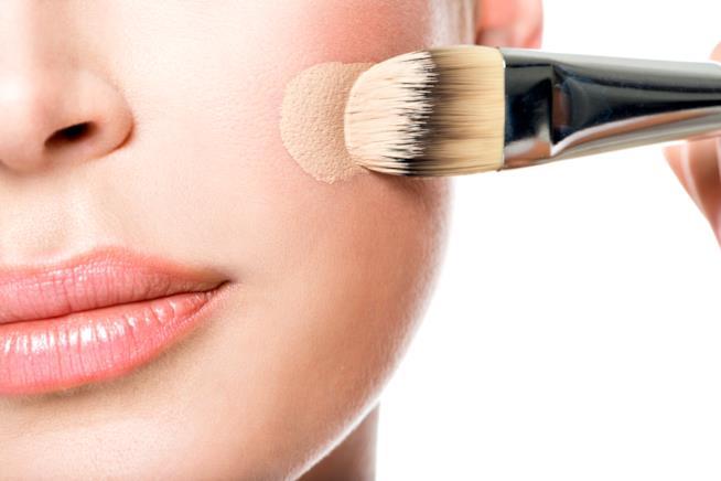 Dettaglio di un viso mentre viene applicato il fondotinta con un pennello